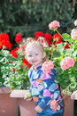 Adorable little child girl in park near flower Bed in summer day. Royalty Free Stock Photo