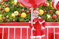 Adorable little child girl in Santa costume with present a Christmas background. Merry Xmas winter holiday concept Royalty Free Stock Photo