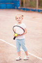 Adorable little child playing tennis with racket and a ball on court Stock Image