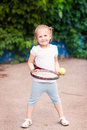 Adorable little child playing tennis with racket and a ball on court Stock Photo