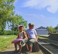 Adorable little children on a railway station, waiting for the train with vintage suitcases. Traveling, holiday and chilhood conce Royalty Free Stock Photo