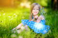 Adorable little girl in blooming meadow on spring day Royalty Free Stock Photo