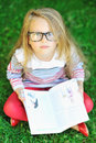 Adorable little girl with a book wearing glasses - outdoors Royalty Free Stock Photo