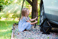 Adorable little girl changing a car wheel outdoors on beautiful summer day Royalty Free Stock Photo