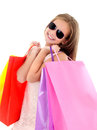 Adorable little girl child in sunglasses holding shopping colorful paper bags Royalty Free Stock Photo