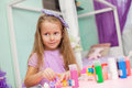 Adorable little girl draws paints at her table in the room this image has attached release Stock Photography