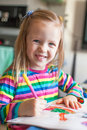 Adorable little girl draws paints sitting at the Royalty Free Stock Photo