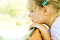 Adorable little girl with eyes gazed deep in thought an seen from one side leans forward her a sunny outdoor setting Stock Images