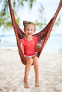 Adorable little girl in hammock swinging at beach Stock Photography