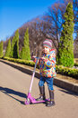 Adorable little girl have fun on the scooter in spring day Stock Images