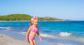 Adorable little girl have fun in shallow water at cute toddler standing exotic beach Royalty Free Stock Photo