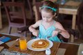 Adorable little girl having breakfast at resort restaurant this image has attached release Stock Image