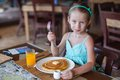 Adorable little girl having breakfast at resort restaurant this image has attached release Stock Photos