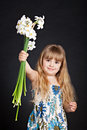 Adorable little girl holding bouquet of narcissuses isolblackated on black Royalty Free Stock Photos