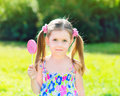 Adorable little girl holding lollipop with two blond ponytails white and pink in her hand outdoor summer portrait Royalty Free Stock Photo
