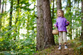 Adorable little girl picking berries in the forest on summer day Stock Photo