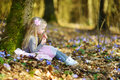 Adorable little girl picking the first flowers of spring in the woods on beautiful sunny spring day Royalty Free Stock Photo