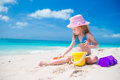 Adorable little girl playing with beach toys on white sandy beach