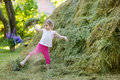 Adorable little girl playing in a haystack on beautiful summer day Stock Photography