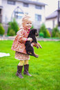 Adorable little girl playing with her puppy outdoor cute in the yard Stock Images