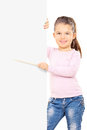 Adorable little girl pointing to a blank panel with stick isolated on white background Stock Images