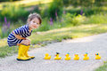 Adorable little girl with rubber ducks in summer park of playing yellow Stock Photo
