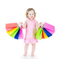 Adorable little girl after sale with her colorful bags curly hair wearing a pink dress is happy and special offer shopping showing Royalty Free Stock Images