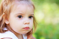 Adorable little girl serene and still her face expresses a thoughtful and contemplative look as she enjoys the outdoors Stock Image