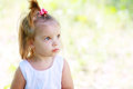 Adorable little girl serene and still her face expresses a thoughtful and contemplative look as she enjoys the outdoors Royalty Free Stock Photography