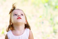 Adorable little girl serene and still her face expresses a thoughtful and contemplative look as she enjoys the outdoors Stock Photos