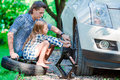 Adorable little girl sitting on a tire and helping father to change a car wheel outdoors on beautiful summer day Royalty Free Stock Photo