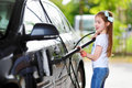 Adorable little girl washing a car on a carwash Royalty Free Stock Photo