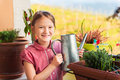 Adorable little girl watering plants on the balcony Royalty Free Stock Photo