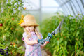 Adorable little girl wearing straw hat and childrens garden gloves playing with her toy garden tools in a greenhouse Royalty Free Stock Photo