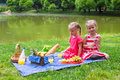 Adorable little girls picnicing in the park at two on picnic Royalty Free Stock Image