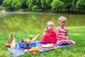 Adorable little girls picnicing in the park at two on picnic Royalty Free Stock Photo
