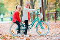Adorable little girls riding a bike at beautiful autumn day outdoors Royalty Free Stock Photo