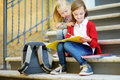 Adorable little schoolgirls studying outdoors on bright autumn day. Young students doing their homework. Education for small kids. Royalty Free Stock Photo