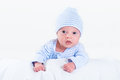 Adorable newborn baby boy playing on his tummy wearing a blue shirt and hat Stock Photography