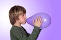 Adorable preteen boy blowing up a purple balloon Royalty Free Stock Photos