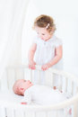 Adorable siblings playing in white nursery newborn baby boy and a toddler girl Royalty Free Stock Image
