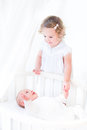 Adorable siblings playing in a white sunny bedroom newborn baby boy and toddler girl holding hands and with round crib Stock Image