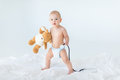 Adorable small baby boy standing on bed and holding stethoscope with teddy bear Royalty Free Stock Photo