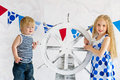 Adorable small mariners cute marine style kids holding wooden steer wheel Royalty Free Stock Images