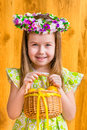 Adorable smiling little girl with long blond hair wearing floral head wreath and holding wicker basket with yellow eggs portrait Royalty Free Stock Photo