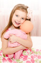 Adorable smiling little girl playing with a doll at home Stock Photo