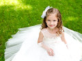 Adorable smiling little girl in princess dress sitting on grass outdoor Royalty Free Stock Photo
