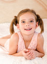 Adorable smiling little girl is resting on a bed Royalty Free Stock Photo