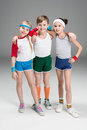 Adorable smiling sporty kids in sportswear standing together  on grey Royalty Free Stock Photo
