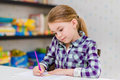 Adorable thoughtful little girl with blond hair sitting at table and drawing with purple pencil white Royalty Free Stock Photos